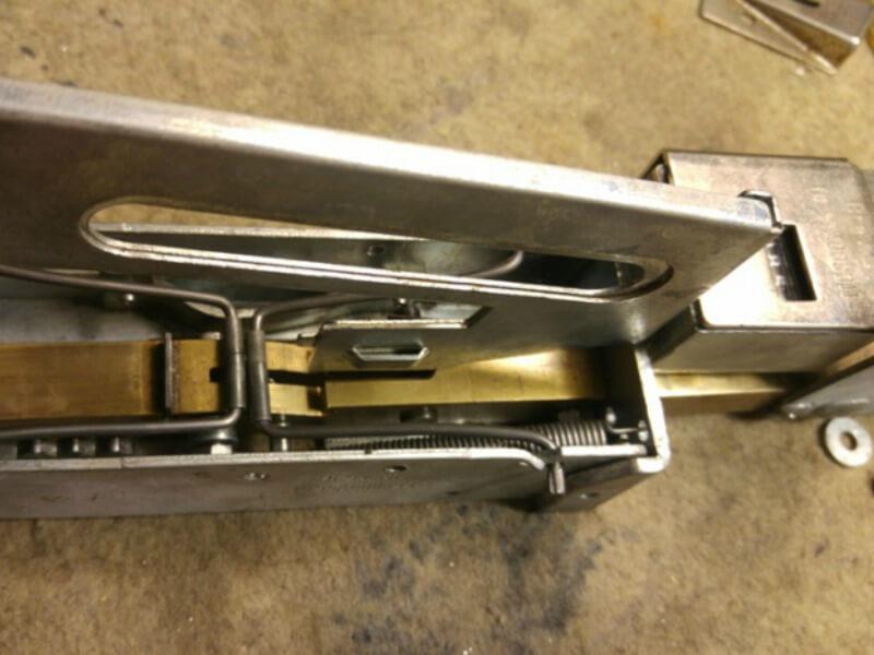 Az alsó rész és a kihúzókart tartalmazó felső rész egymáshoz illesztése. A nagy rugó réz rúdra akasztása.